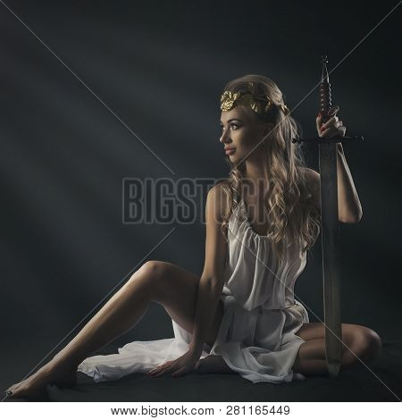Goddess Young Woman On Darkt Bg  With Sword Studio Shot