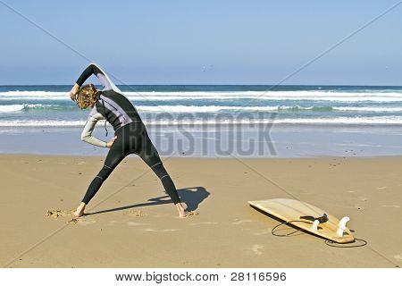 Young guy doing exercises before going to surf