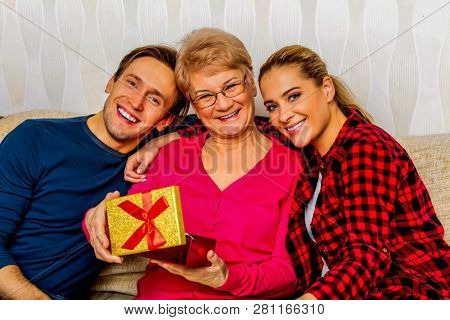 Happy adult kids with elderly mother on couch. Mothers day concept.