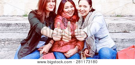 Happy Multiracial Young Women Thumbs Up Sitting Outdoors At Day Time - Three Best Female Friends In