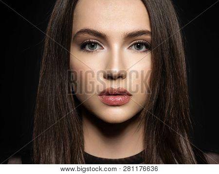 Woman with beauty long brown hair. Fashion model with long straight hair. Fashion model posing at studio.Pretty woman with long straight brown hair looking at camera.