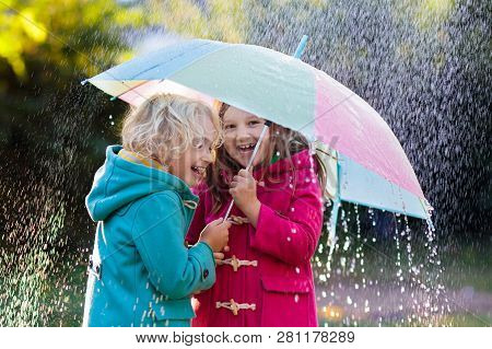 Kids With Colorful Umbrella Playing In Autumn Shower Rain. Little Boy And Girl In Warm Duffle Coat P