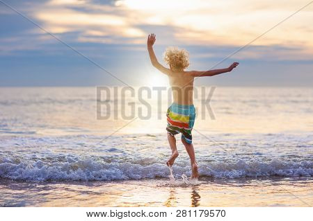 Child Playing On Ocean Beach. Kid Jumping In The Waves At Sunset. Sea Vacation For Family With Kids.