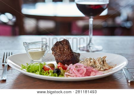 beef medallions with mushrooms, lettuce, olives, cherry tomatoes and onions. served with red wine and white sauce, served on a wooden table in the restaurant poster