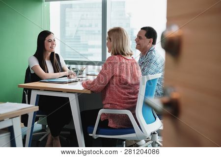 Woman Working As Investment Advisor Talking To Customers In Office