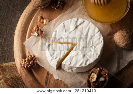 Camembert And Brie Cheese On Wooden Background With Tomatoes, Letuce And Garlic. Italian Food. Dairy