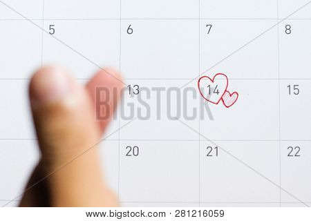 14 Feburary With Mini Heart Hand Sign And Red Or Pink Heart On Calendar - Valentine's Day Concept.