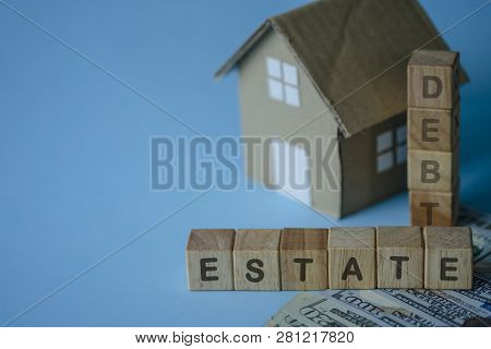 House Model And Debt Estate Wording On Wooden Cubes On Blue Background.saving And Investment To Real