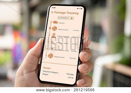 Man Hand Holding Phone With App Tracking Delivery Package On The Screen Background Of A City Street