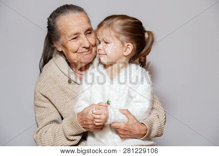 ?ute gray long haired grandmother in knitted sweater hugs granddaughter with chicken pox, white dots, blisters on face. Concept family photo session, different generations, nursing child poster