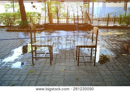 Two Chair On Cement Bricks With Flare From The Morning Sun At The Garden With Water From Sprinkler