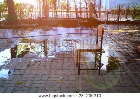 The Chair On Cement Bricks With Flare From The Morning Sun At The Garden With Water From Sprinkler