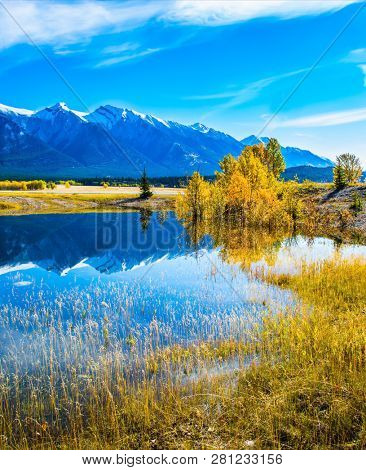 Concept of active and ecological tourism. Indian Summer in the Rockies. Rocky Mountains are reflected in the turquoise smooth water of Lake Abraham