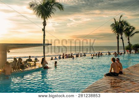 Bali, Indonesia - February 4, 2013: Tourists Enjoy A Bali Vacation By The Pool And Beach. Bali Is Po