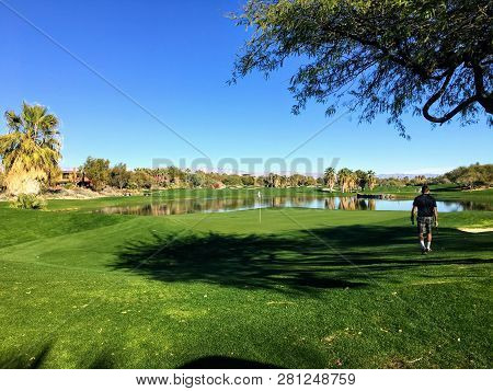 A Young Male Golfer Walking Towards The Green On A Par 4 Surrounded By Water On A Golf Course In The