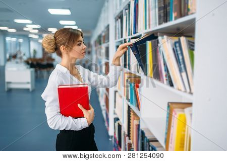 Young woman looking book at the shelf in library