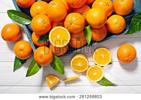 Fresh orange fruits with leaves on wooden table. Healthy food concept. Vitamin C poster
