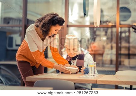 Positive Kind Woman Putting A Bowl With Soup On The Table