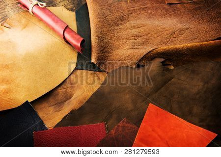 Selecting leather. Leather craft. Colorful pieces of beautifully colored or tanned leather on leather craftman's work desk .