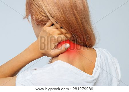 Closeup Studio Portrait Of Unhealthy Young Blonde Female In White Top With Pain In Her Neck And Back