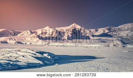 Sunset in Antarctica. Snow on mountain range against colorful pink and blue sky. Big glacier in front. Nature background. Stunning winter landscape. The wilderness. Beauty of wild South pole