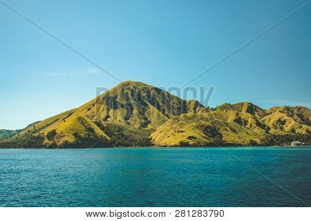 Greens covered hills washed by the calm ocean. Komodo island, Indonesia. Overwhelming marine landscape. Stunning Indonesian shoreline. The wilderness. Ideal background for the collages, illustrations.