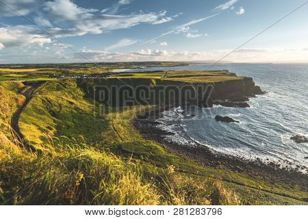 Sunlit Northern Ireland shoreline. The green grass covered land next to the ocean water surface. The local road among the wild untouched nature. The stunning bay under the blue cloudy sky. Serenity.