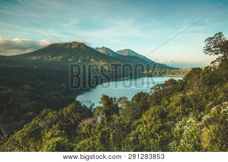 The lake Batur surrounded by the greens and volcano. Bali island, Indonesia. Picturesque overview of the water surface among the dense woods. Popular tourist attraction. Amazing Balinese landscape.
