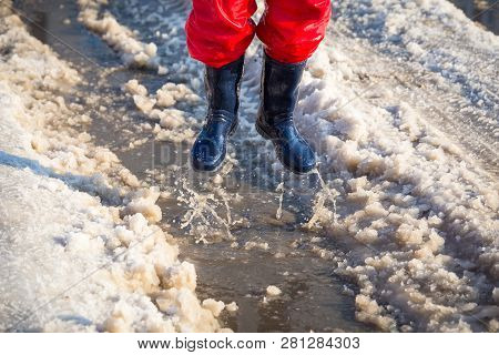 Kid In Blue Rainboots Jumping In The Ice Puddle With Melting Snow At Sunny Spring Day, Outdoors