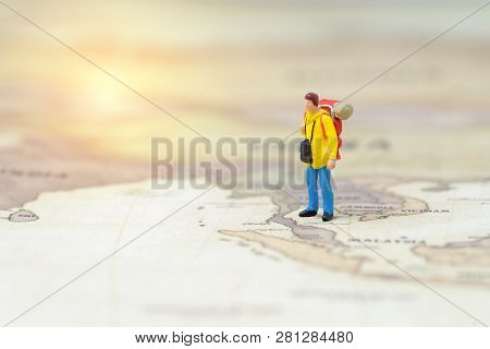 Miniature people young man backpacker standing on vintage world map, Travel, tourism, vacation or wanderlust life concept, plan for next destination, new adventure journey. poster