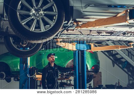 Modern Auto Service And Caucasian Car Mechanic. Broken Vehicles On A Lifts. Automotive Industry.