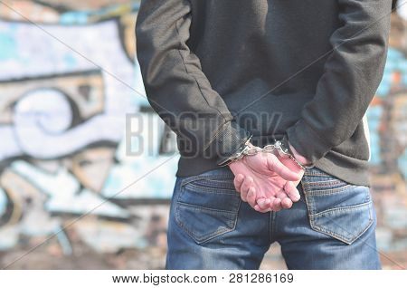 Close-up Of Male Hands, Handcuffed Against A Graffiti Background