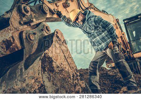 Construction Industry. Heavy Equipment Operator Job. Excavator And Caucasian Worker In Hard Hat. Men