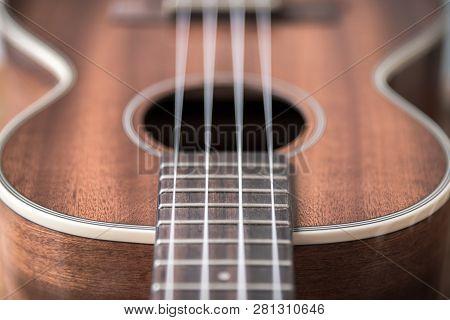 Tenor Ukulele Close-up Of Frets And Strings On Fretboard Near Ukulele Body
