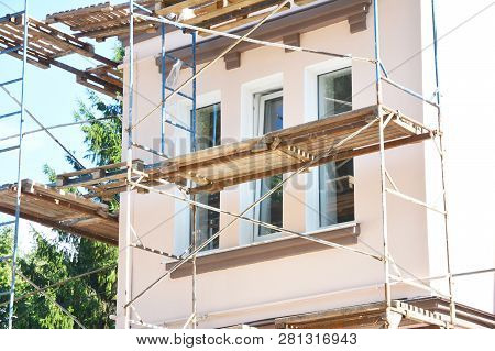 Painting And Plastering Exterior House Scaffolding Wall. Home Facade Insulation, Sctucco And Paintin