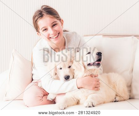 Smiling girl sit hugging cute puppies on sofa