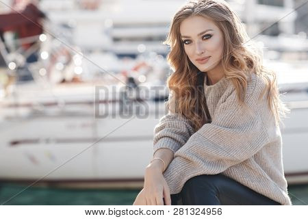 Portrait Of Beautiful Woman With Long Curly Blond Hair On Gray Background. Young Woman With Natural