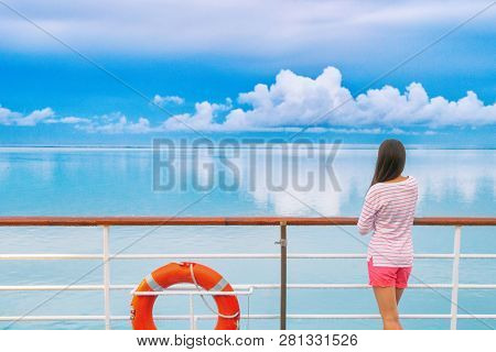 Cruise ship luxury travel woman on deck looking away in Tahiti. Serene still ocean water landscape. Tourism vacation holidays in French Polynesia.