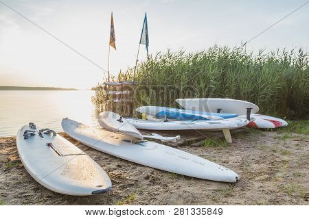 Old-school Windsurfing Boards On The Shore Of The Lake.
