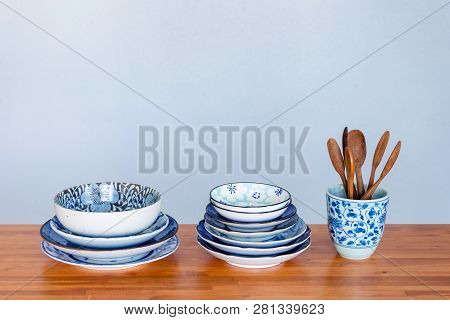 Stack Of Ceramic Tableware On Wooden Table.