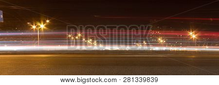 The Motorway At Night. The Car Moves At Fast Speed At The Night. Blured Road With Lights With Car On