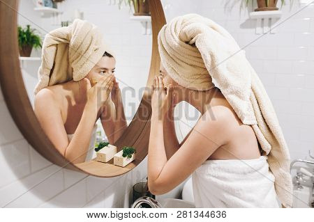 Young Happy Woman In Towel Applying Organic Face Scrub And Looking At Round Mirror In Stylish Bathro