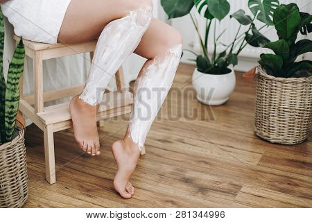 Young Woman In White Towel Applying Shaving Cream On Her Legs In Home Bathroom With Green Plants. Sk