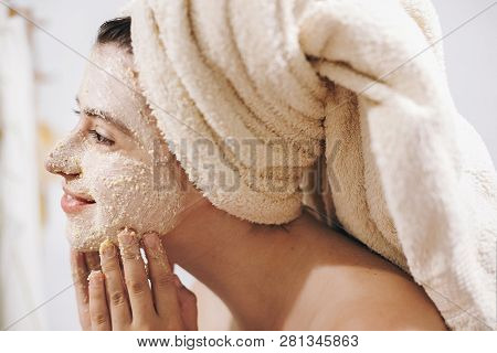 Skin Care Concept. Young Happy Woman In Towel Making Facial Massage With Organic Face Scrub Close Up