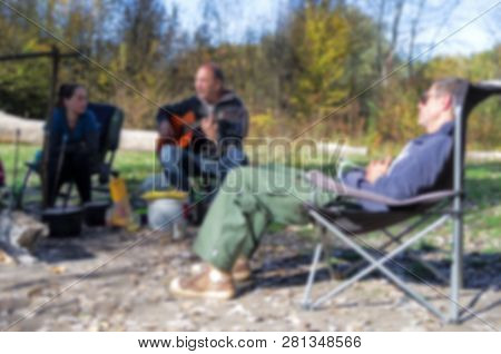 Blurred Background Out Of Focus. Tourist Camping With People And Guitar Theme Bokeh. Defocused Camp