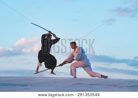 Concentrated Men, In Japanese Clothes, Are Practicing Martial Arts With A Traditional Japanese Weapo