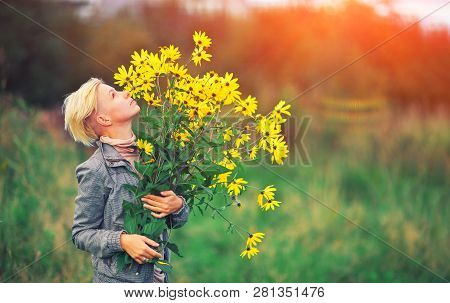 Beautiful Blonde Woman Enjoying Flower Field, Hipster Girl Holding A Bouquet Of Wildflowers In Her H