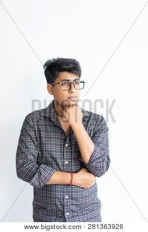 Pensive Nerdy Guy Thinking Over Solution. Young Man In Glasses Leaning Chin On Hand And Staring Into