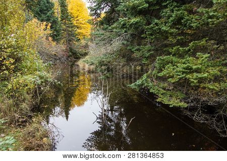 Autumn River Reflections. Beautiful Autumn Foliage Reflected In The Water Of A Small River In The Hi