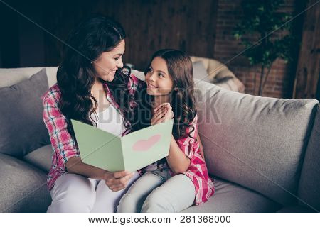 Close up photo two people mum little daughter giving postcard with mommy poem unexpected sweet cute reading delighted wear pink plaid shirts flat apartment room sit cozy couch sofa divan poster